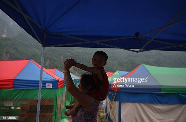 An earthquake survivor carries her son at a refugee camp on June 5, 2008 in Shifang, Sichuan province, China. More than 69,000 people are now known...