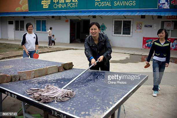 An earthquake survivor cleans a table for children who play table tennis in the settlement of Leigu Township on May 10 2009 in Beichuan County of...