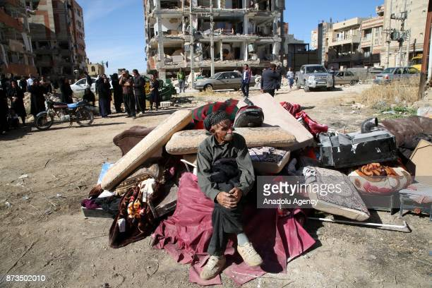 An earthquake survivor elderly man wait with his belongings at the outside of the damaged buildings in Sarpole Zahab town of Kermanshah Iran on...