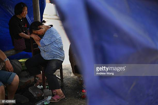 An earthquake survivor falls asleep at a refugee camp on June 5, 2008 in Shifang, Sichuan province, China. More than 69,000 people are now known to...
