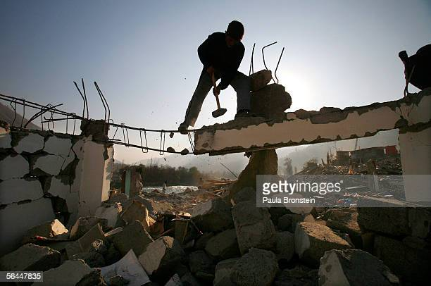 An earthquake survivor hammers by hand at the rubble December 17 2005 in the town of Balakot Pakistan The lack of bulldozers still posing a problem...