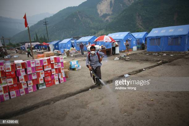 An earthquake survivor helps to disinfect a refugee camp on June 5, 2008 in Shifang, Sichuan province, China. More than 69,000 people are now known...