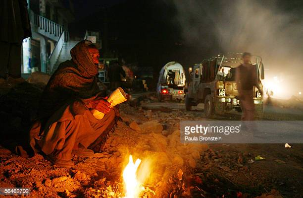 An earthquake survivor tries to keep warm by a fire along a street December 19 2005 in downtown Balakot Pakistan Lack of snow is giving survivors of...