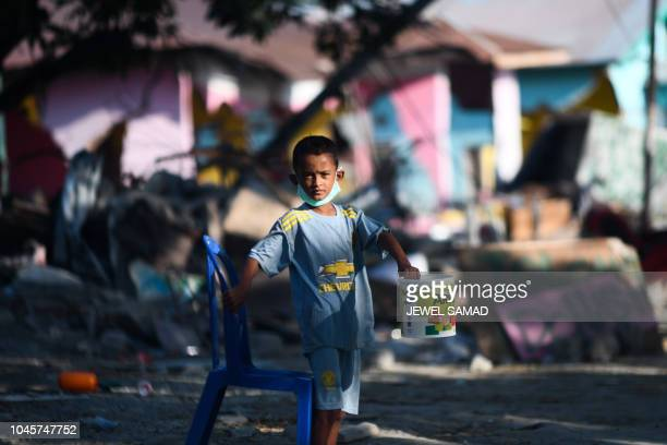 An earthquakeaffected child asks for donations along a road in Donggala in Indonesia's Central Sulawesi on October 5 following the September 28...