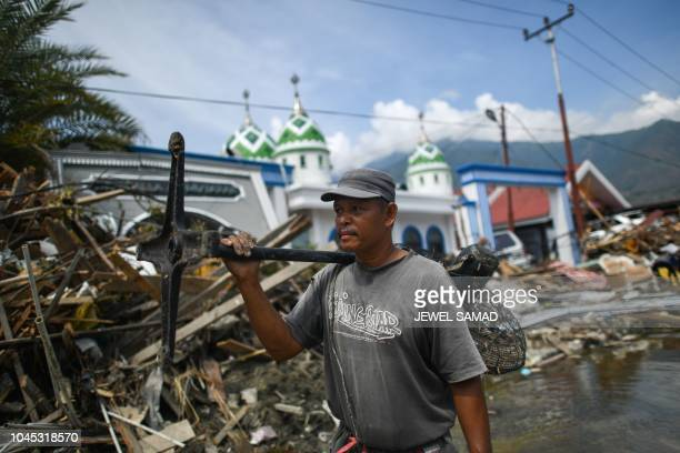 An earthquakeaffected resident carries a fan he salvaged from a collapsed market in Palu Indonesia's Central Sulawesi on October 4 after an...