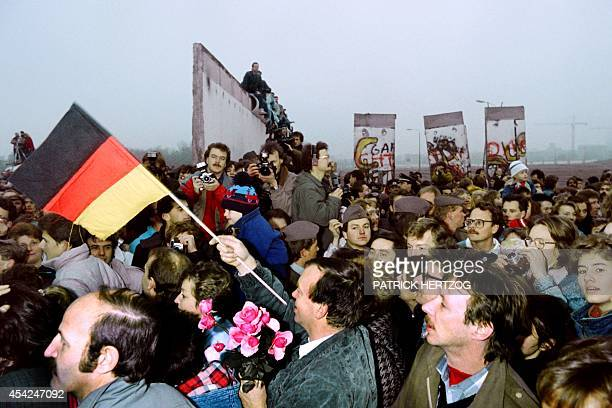 An East Berliner with West german flag and flowers enters West berlin amidst a crowd of East germans flooding through the recently made opening in...