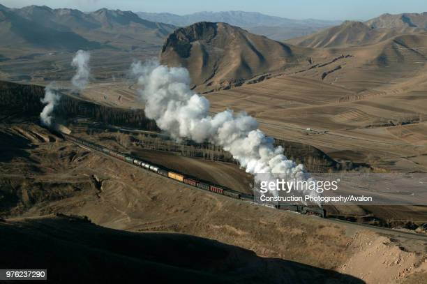 An east bound freight bound for Daban emerges from tunnel number four on the Jing Peng pass leaving wraiths of steam oozing from the tunnel mouth The...