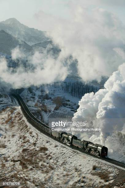 An east bound rake of coal empties emerges from tunnel number four behind two QJ Class 2102s on the Jing Peng section of the JiTong Railway in Inner...