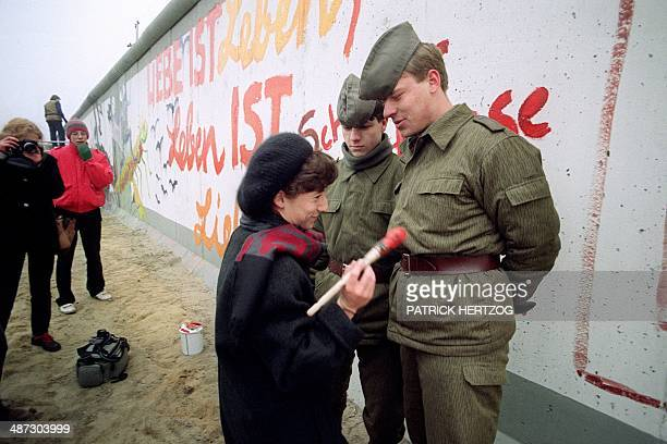An East German artist offers to paint Vopos' uniforms trying to prevent her from going on painting on the Berlin Wall on November 21 1989 in Berlin...