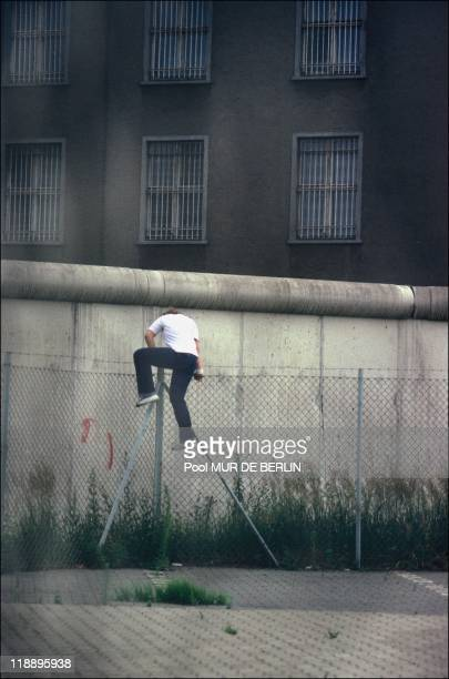 An East German climbs over the wall in East Berlin Germany