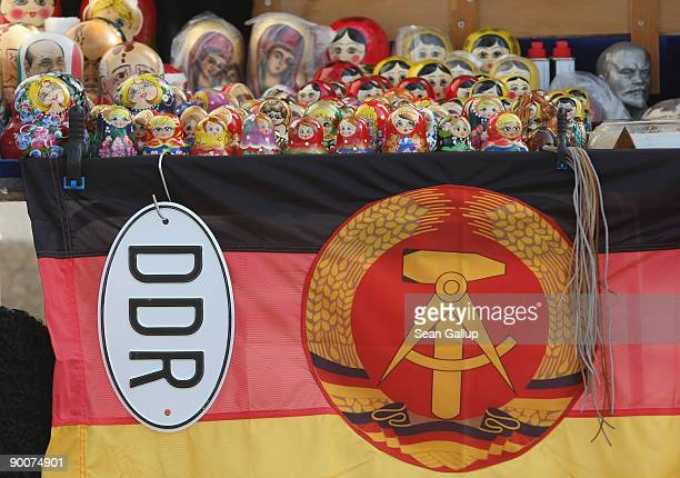 An East German communistera flag an East German car symbol matrioshka dolls and a bust of Lenin await tourists at an outdoor stand near Checkpoint...