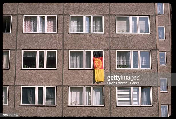 An East German flag hangs from an apartment window on the first election day after the fall of the Berlin Wall East Berlin East Germany