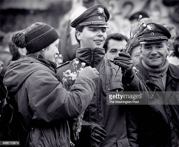West Berlin Germany An East German woman gives flowers to West German border guards at the opening of the Berlin Wall at Potsdamer Platz Washington...