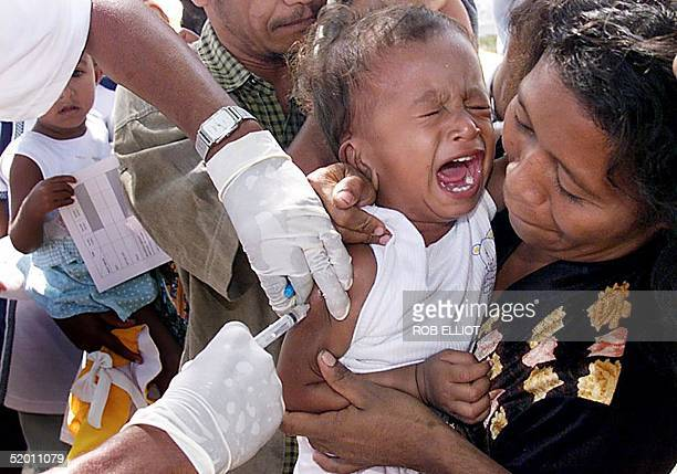 An East Timorese baby in the arms of his mother cries as he receives an innoculation for measles at an immunization outlet in Dili 19 October 1999...