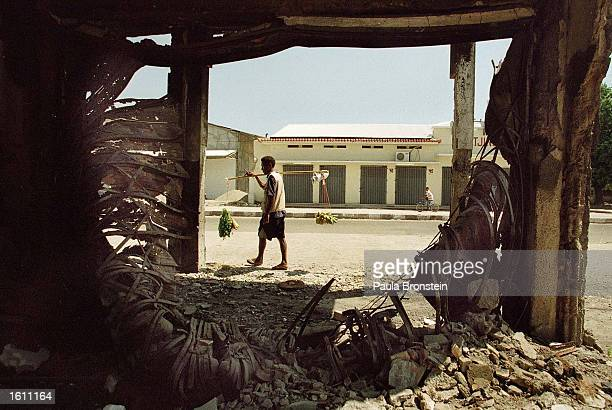An East Timorese carrying bananas and vegetables walks down an empty street August 27 2001 in Dili The burned out building in the foreground is left...
