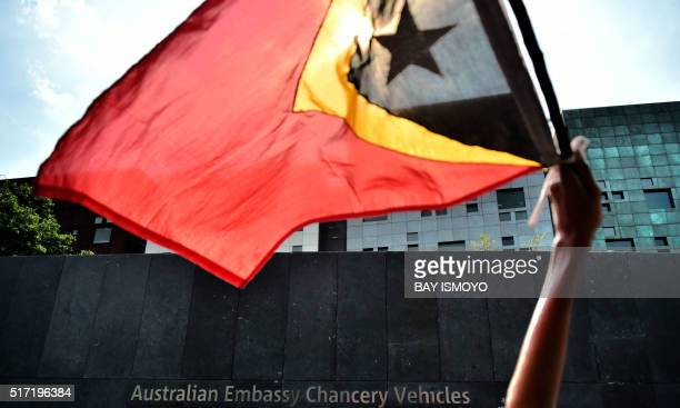 An East Timorese student living in Indonesia holds up his national flag during a rally in front of the Australian embassy in Jakarta on March 24 2016...