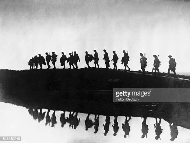 An East Yorkshire regiment of British troops in silhouette negotiate their way around a rainwaterfilled shell crater near the Western Front during...