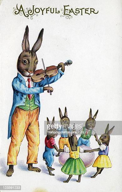 An easter bunny plays violin for his children in this fantasy postcard printed early 20th century in Rochester New York