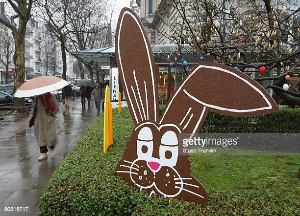 An easter rabbit gets wet in the rainas shoppers walk by with umbrellas in Eppendorf as weather forcasters predict wet weather for the easter...