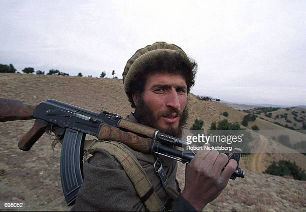 An Eastern Alliance soldier from the Jalalabad area walks near a US bombing target December 18 2001 in Tora Bora Afghanistan The entire hillside was...