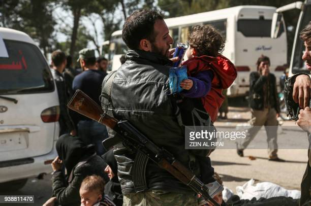 TOPSHOT An EasternGhouta evacuated Syrian rebel fighter slinging a Kalashnikov assault rifle helps a child drink from a juice can after arriving in...