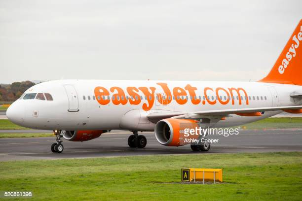 an easyjet plane taxiing towards the runway at manchester airport, uk. - easyjet stock pictures, royalty-free photos & images