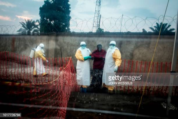 TOPSHOT An Ebola patient is lead by two medical workers into a Biosecure Emergency care Unite on August 15 2018 in Beni The new ETC will hold ten...