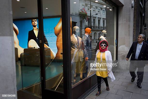 An eccentric looking woman passesby Suitsupply a fashion shop on Vigo Street in London's West End Wearing large owllike glasses and a bright red...