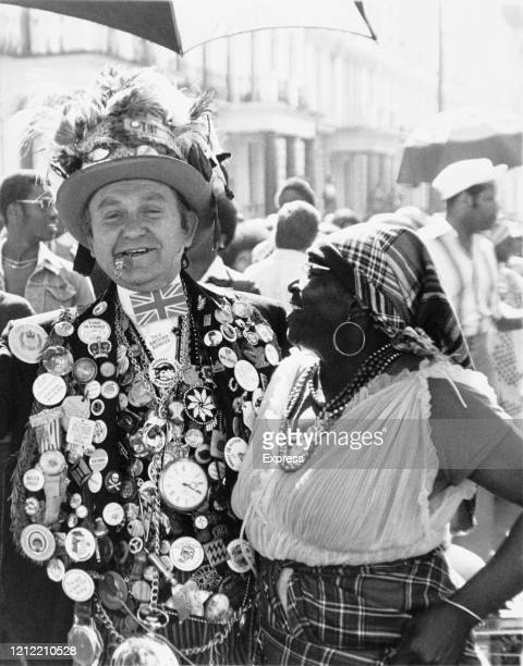 An eccentric man, wearing jacket decorated with a variety of pins and gadget, chats with a woman at the Notting Hill Carnival, London, UK, 30th...