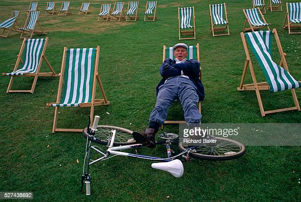 An eccentric middleaged man rests his legs on his bicycle while open mouthed and snoring snatches forty winks on a striped deck chair in London's...