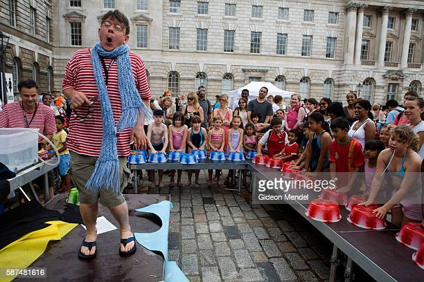 An eccentric performer leads a children's drumming and music workshop which uses water and plastic water bowls in the Somerset House courtyard. This...