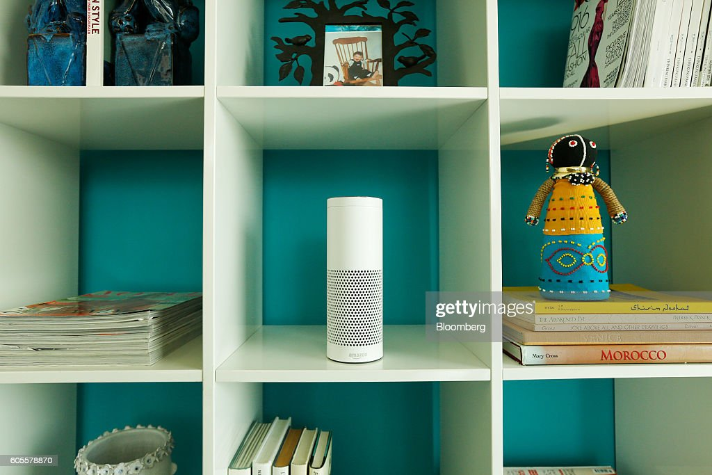 An 'Echo' device, center, stands on display in a set of shelves during the U.K. launch event for the Amazon.com Inc. Echo voice-controlled home assistant speaker in London, U.K., on Wednesday, Sept. 14, 2016. The Seattle-based company today announced that its Echo product line will be available in the U.K. and Germany starting in the fall, the first time the gadget will be available outside the U.S. Photographer: Luke MacGregor/Bloomberg via Getty Images