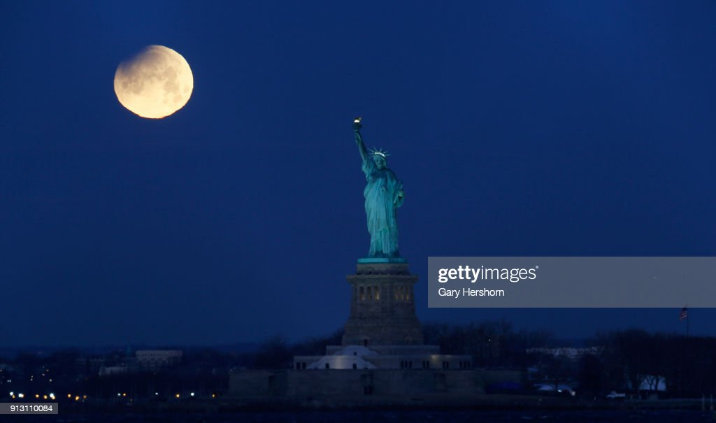 An eclipse begins to show on the super blue blood moon as it sets next to the Statue of Liberty on January 30, 2018 in New York City.