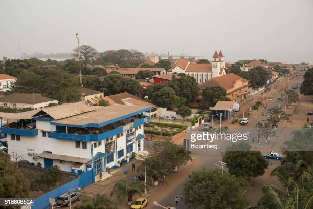 An Ecobank Guinea Bissau bank branch left and Bissau Cathedral also known as Se Catedral de Nossa Senhora da Candelaria stand among residential and...
