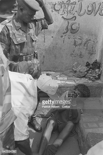 An ECOMOG soldier maltreats a woman who has been arrested