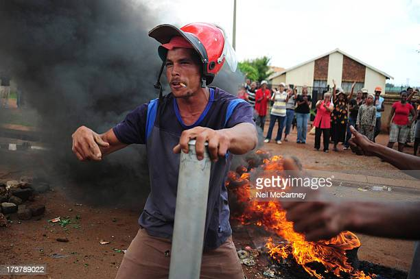 An Edenpark resident gestures to cameras with a Red Ant helmet before burning it along with a few shields, helmets and overalls that were left behind...