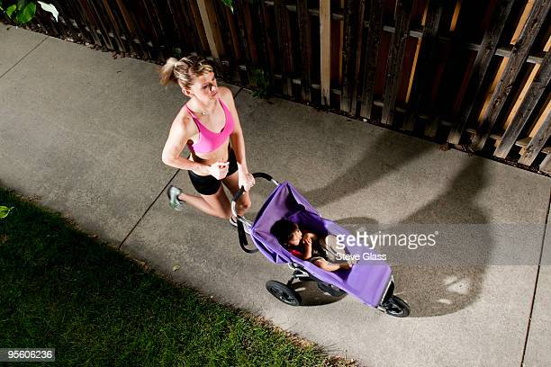 An edgy-looking, athletic young woman in a sports bra enjoys a run on a suburban sidewalk with a bab