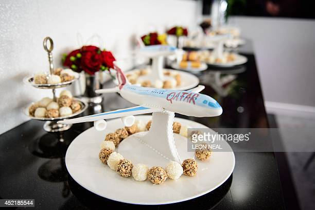 An edible passenger plane is seen in the Qatar Airways chalet at the Farnborough air show in Hampshire England on July 15 2014 The biennial event...