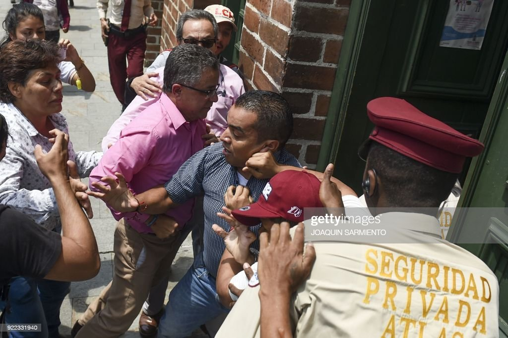 An education official (C-L) tries to enter the Secretariat of Education building as students, teachers and social activists hold a demonstration demanding improvements in education, in Medellin, Colombia, on February 21, 2018. /