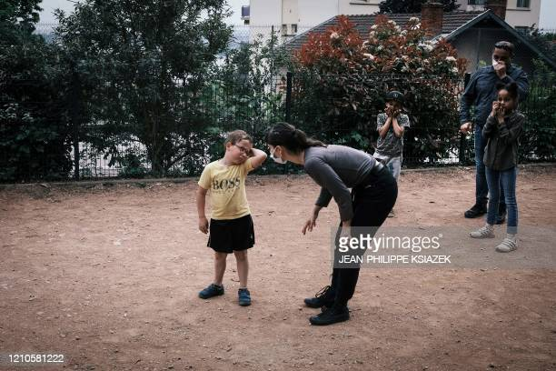An educator wears a face mask as she speaks with a boy on April 20 2020 in the L'etoile du berger institution for children in social or parental...