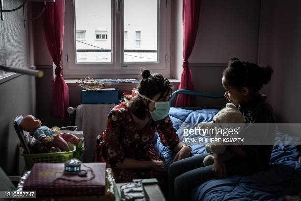 TOPSHOT An educator wears a face mask as she speaks with a girl on April 20 2020 in the L'etoile du berger institution for children in social or...