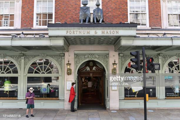 An eEmployee wearing personal protective equipment including a face mask and a visor staffs the entrance to upscale department store Fortnum and...