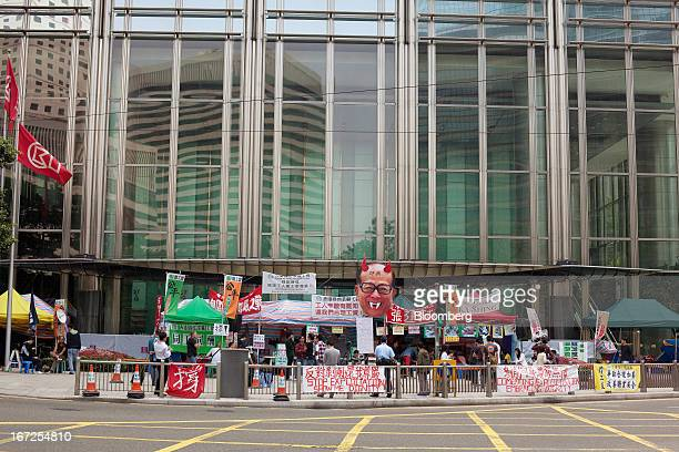 An effigy of Billionaire Li Kashing is displayed along with banners as dockworkers protest in front of the Cheung Kong Center in Hong Kong China on...