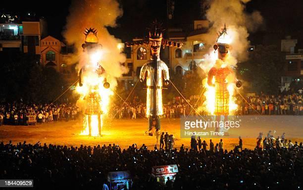 An effigy of demon king Ravana Meghnath and Kumbhakarna burns during Dussehra celebrations in Ramlila ground on October 13 2013 in Gurgaon India...