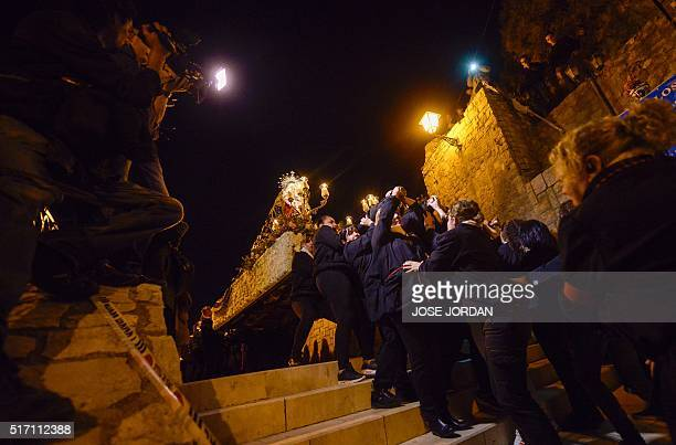 An effigy of Jesus Christ on the cross is carried down steps during the Cristo de la Fe populary known as the gypsy Christ parade during a Holy Week...