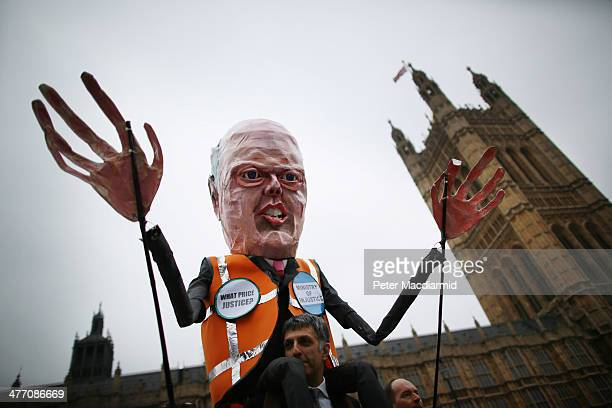An effigy of Justice Sectretary Chris Grayling is held up as barristers and solicitors hold a demonstration outside Parliament on March 7 2014 in...