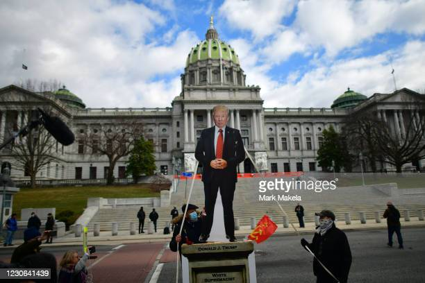 An effigy of President Donald Trump is lowered while people demonstrate against the president outside the Pennsylvania Capitol Building on January...