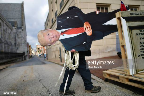 An effigy of President Donald Trump is wheeled towards the Pennsylvania Capitol Building to demonstrate against the president on January 17, 2021 in...