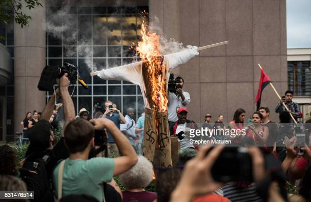 An effigy of US President Donald Trump dressed in khakis and a white shirt covered in swastikas is set ablaze during a protest against racism and the...