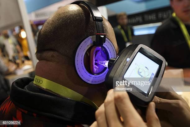 An eFit 3D ear scanner produced by United Sciences LLC is used to measure customfit 3Dprinted Snugs Earphones for Echobox Audio LLC headphones during...
